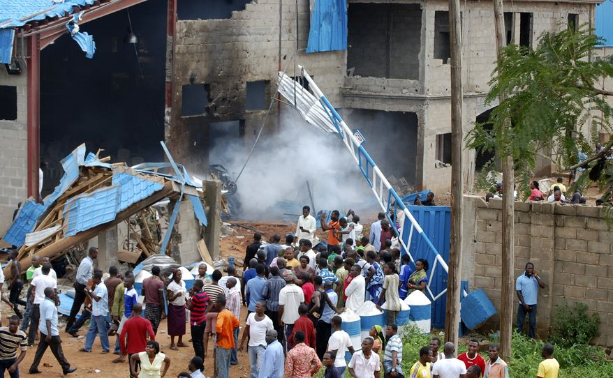 Nigerians gather outside a church following a blast in Kaduna, Nigeria, on Sunday, June 17, 2012. Bombings at three churches rocked the country's north, officials said, prompting protests in an area that has been strained by religious tensions. (AP Photo/Olu Ajayi)