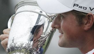 Webb Simpson holds up the championship trophy after the U.S. Open Championship golf tournament Sunday, June 17, 2012, at The Olympic Club in San Francisco. (AP Photo/Charlie Riedel)