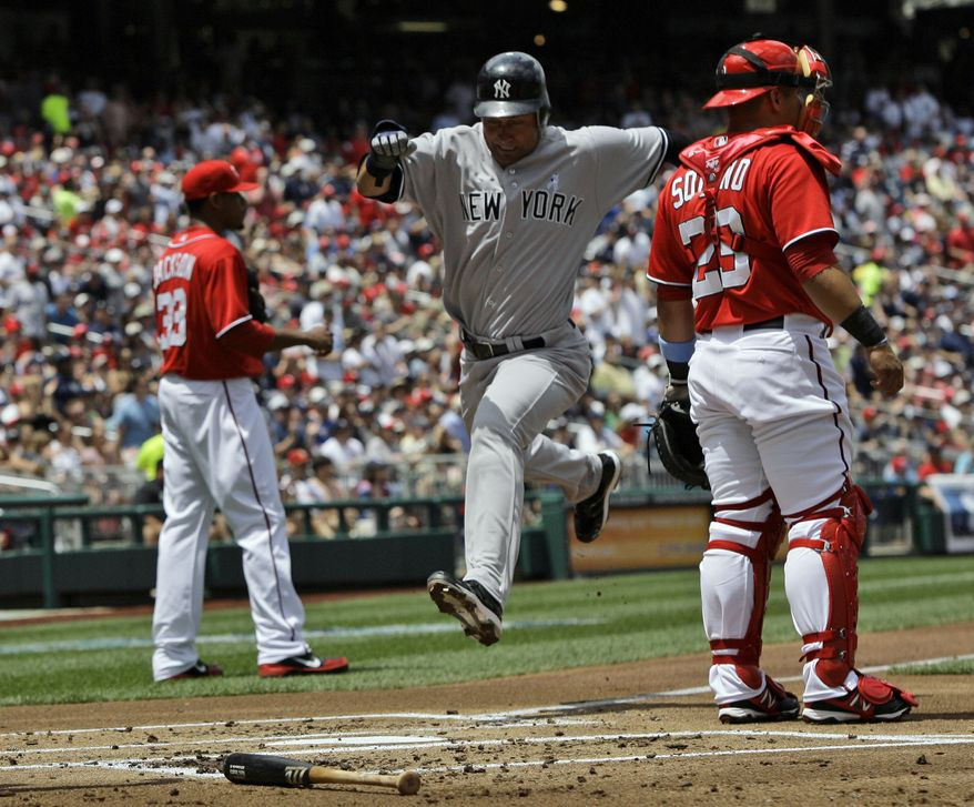 New York Yankees' Derek Jeter, center, scores on a sacrifice fly by Mark Teixeira as Washington Nationals catcher Jhonatan Solano (23) looks on during the first inning of a baseball game at Nationals Park, Sunday, June 17, 2012, in Washington. The Yankees won 4-1. (AP Photo/Alex Brandon)