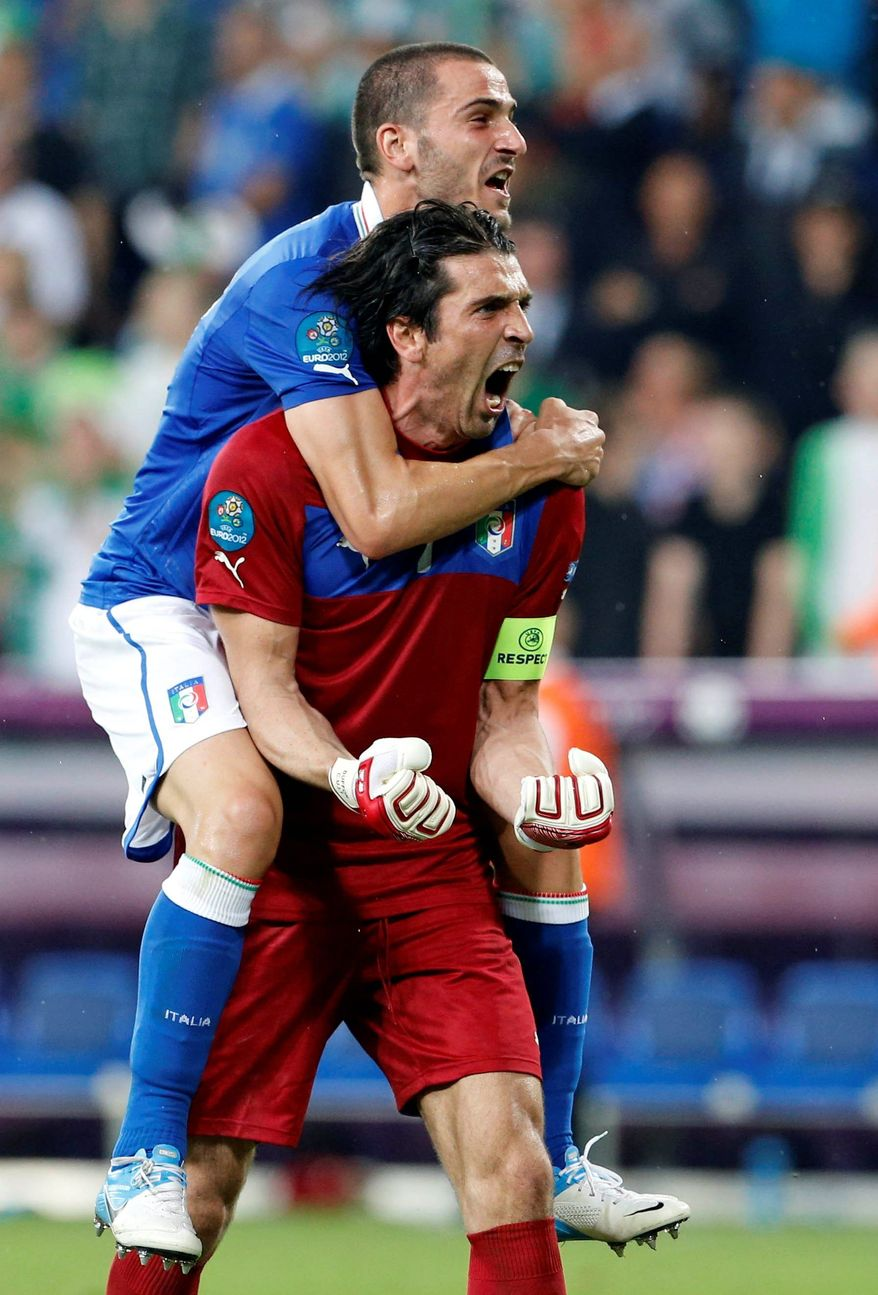 Italy's Leonardo Bonucci goes along  for the ride as he hops on the back of goalkeeper Gianluigi Buffon to celebrate a win over Ireland. (Associated Press)