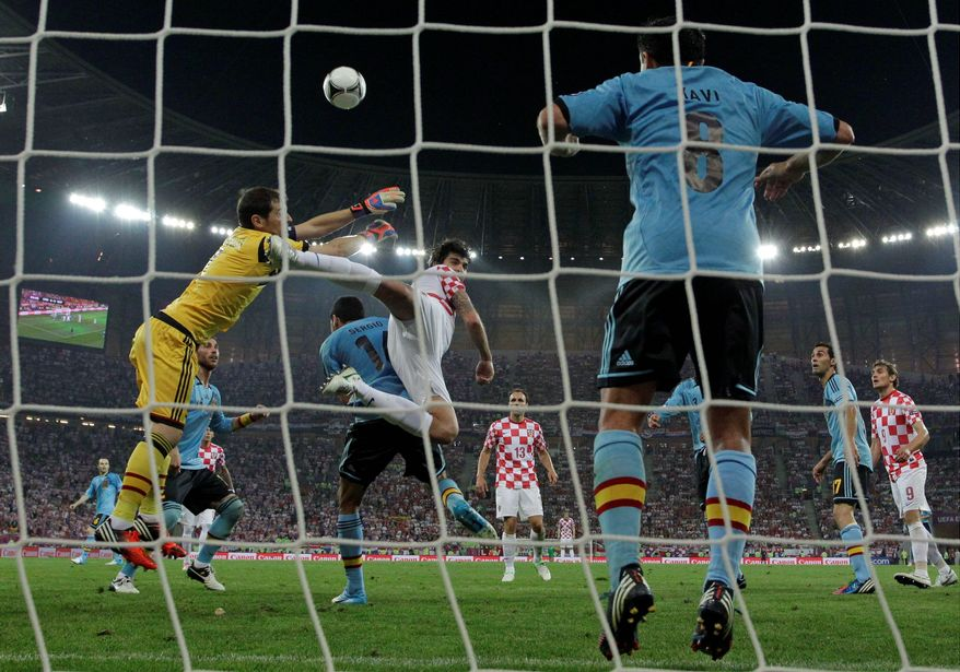 Spain goalkeeper Iker Casillas makes a save in front of Croatia's Vedran Corluka Monday during the Euro 2012 soccer championship Group C match against Croatia in Gdansk, Poland. (Associated Press)