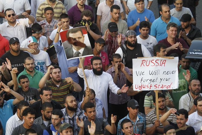 Protesters chant slogans against the Syrian regime and Russia's support of President Bashar Assad, seen in a poster with a shoe on his face, in the southern port city of Sidon, Lebano