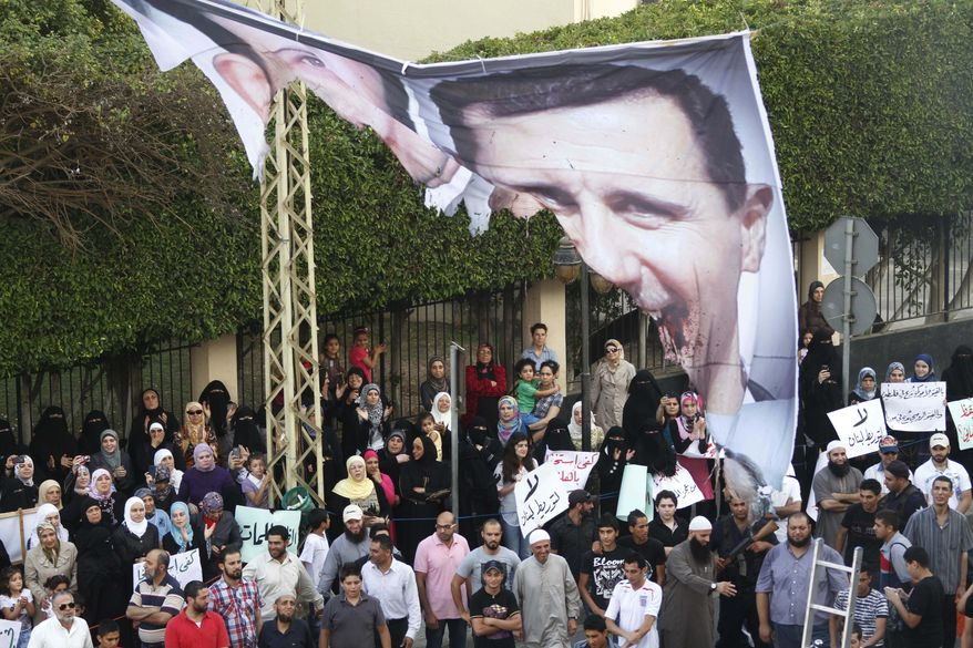 Protesters chant slogans against the Syrian regime and Russia's support of President Bashar Assad as they hold a burned banner depicting Mr. Assad (right) and his brother, Maher Assad (left), in the southern port city of Sidon, Lebanon, on Sunday, June 17, 2012. (AP Photo/Mohammed Zaatari)