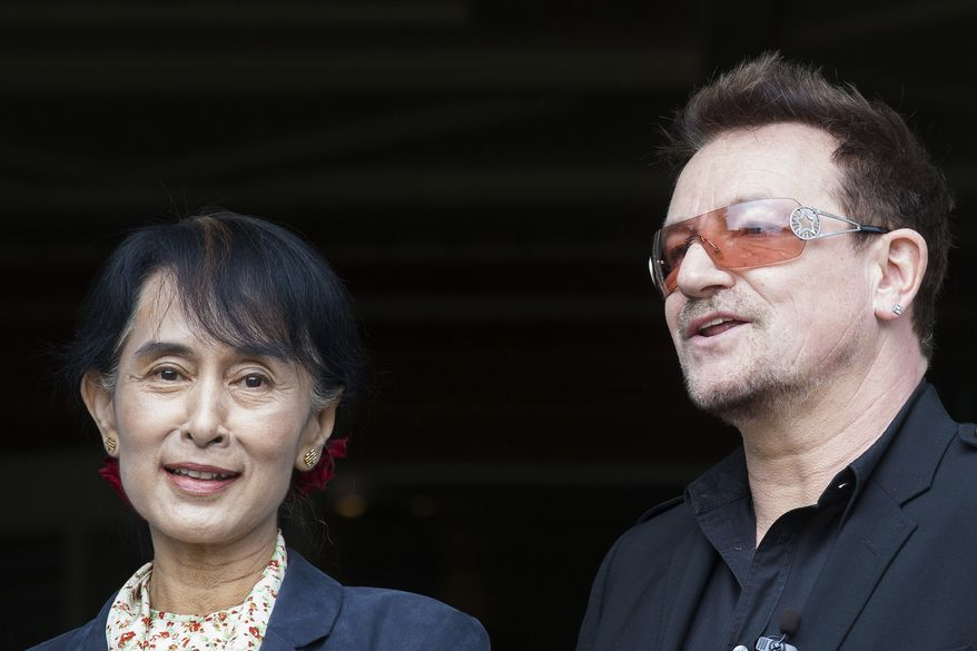 Myanmar opposition leader Aung San Suu Kyi (left) and Irish singer and activist Bono pose for the media after attending a conference of the Oslo Forum, an international network of armed conflict mediation practitioners, at the Losby Gods resort near Oslo on Monday, June 18, 2012. (AP Photo/Markus Schreiber)