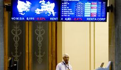 A broker puts on his tie after arriving June 18, 2012, at the Stock Exchange in Madrid. (Associated Press)