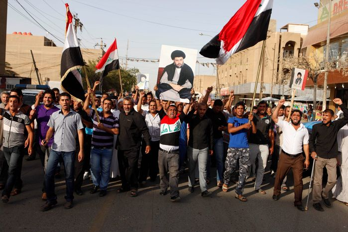 Hundreds of followers of Shiite cleric Muqtada al-Sadr demonstrated this month in front of a local Iraqi TV station in Baghdad that accused them of receiving their instructions from Iran. (Associated Press)