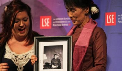 Myanmar opposition leader Aung San Suu Kyi (right) receives a picture of her father as a birthday gift after taking part in a round table at the London School of Economics and Political Science in London on Tuesday, June 19, 2012. (AP Photo/Elizabeth Dalziel)