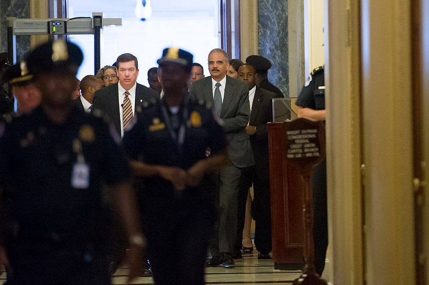 Attorney General Eric H. Holder Jr. (right) arrives at the U.S. Capitol in Washington on Tuesday, June 19, 2012, to meet with the House leadership to discuss the congressional investigation into the botched anti-gunrunning Fast and Furious operation. (Andrew Harnik/The Washington Times)