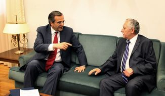 Antonis Samaras (left), leader of Greece's conservative New Democracy party, meets with Democratic Left party chief Fotis Kouvelis at the Greek parliament in Athens on Monday, June 18, 2012. (AP Photo/Petros Giannakouris)