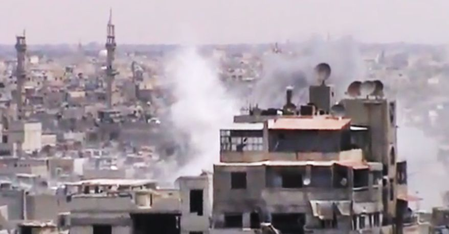This image made from amateur video released by the Shaam News Network and accessed on Monday, June 18, 2012, purports to show smoke rising from buildings in Homs, Syria. (AP Photo/Shaam News Network via AP Video)