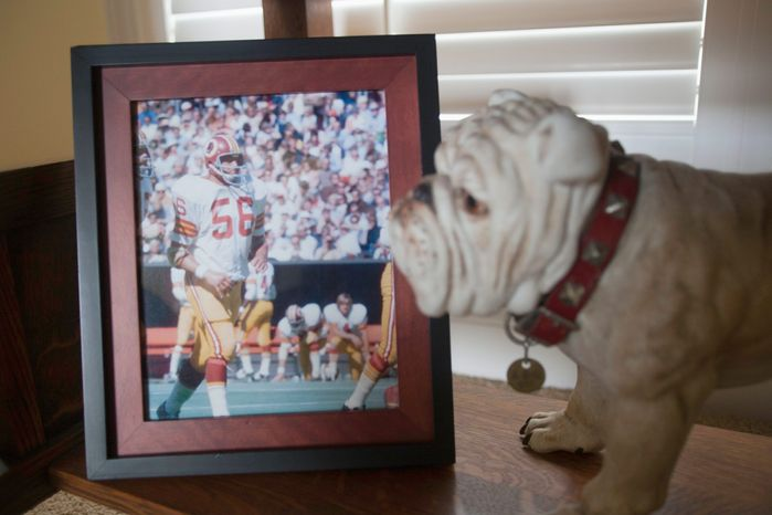 A picture of Len Hauss from his playing days with the Washington Redskins is displayed in Hauss' Jesup Georgia home next to a statue of famed University of Georgia mascot Uga. (Richard Burkhart/Special to The Washington Times)
