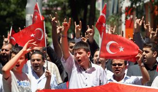Turks hold national flags as they march in Ankara on Wednesday. They were protesting the deaths of soldiers a day earlier, when Kurdish rebels attacked Turkish military units with mortars and rocket-propelled grenades in the Daglica area of Hakkari province, which borders northern Iraq Kurdish areas in southeastern Turkey. Reportedly, at least eight soldiers and 26 rebels died. (Associated Press)