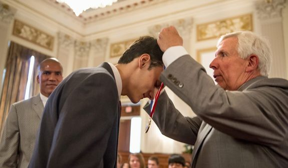 "Alexander Pauken of Great Falls receives his Congressional Award Gold Medal from Rep. Frank R. Wolf, Virginia Republican. ""They're giving back a lot to their communities to earn what they get here,"" said the father on one recipient. (Andrew Harnik/The Washington Times)"