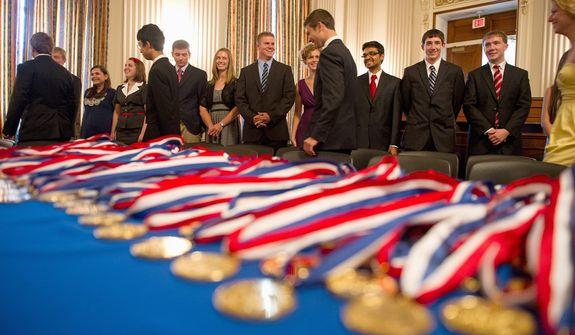 Congressional gold medals are displayed before being presented to young men and women filing in at the beginning of their awards ceremony Wednesday at the Cannon House Office Building. The 276 youth were honored for completing 400 hours of voluntary public service activities, 200 hours each of personal development and physical fitness activities, as well as an expedition and exploration activity. (Andrew Harnik/The Washington Times)