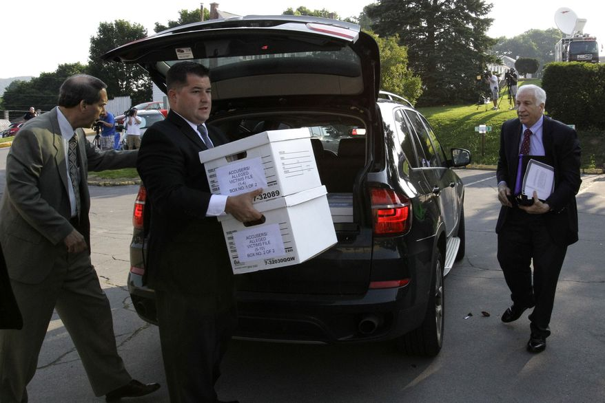 Former Penn State University assistant football coach Jerry Sandusky (right) arrives June 20, 2012, with his attorney Joe Amendola (left) as case files are unloaded at the Centre County Courthouse in Bellefonte, Pa. Sandusky is charged with 51 counts of child sexual abuse involving 10 boys over a period of 15 years. (Associated Press)