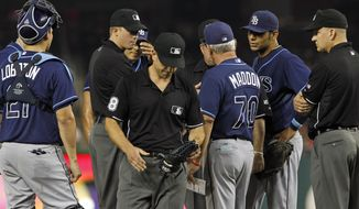 Umpire Chris Guccione leaves with the glove of Tampa Bay Rays relief pitcher Joel Peralta during the eighth inning against the Washington Nationals on Tuesday, June 19, 2012, in Washington. Peralta was ejected in the eighth inning for having a foreign substance on his glove. (AP Photo/Alex Brandon)
