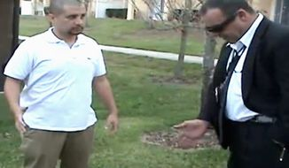 An image from a Sanford, Fla., police video posted on gzlegalcase.com by George Zimmerman's defense team shows him speaking to an investigator at the scene of Trayvon Martin's fatal shooting Feb, 27, the day after the teen was killed. (Associated Press)