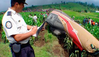 A Guatemalan policeman takes notes on about helicopter that crashed 124 miles northwest of Guatemala City in 2003 while transporting 1,675 pounds of cocaine. (Associated Press)