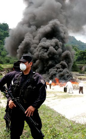 Salvadoran police (above) show reporters more than 661 pounds of cocaine from Colombia seized in the port of Acajutla, El Salvador, in 2008. At right, a policeman stands guard as 1 ton of cocaine from Columbia, seized near El Salvador's coast, is incinerated in 2007. At top, Guatemalan police prepare 7,300 pounds of cocaine for incineration in 2003. (Associated Press)