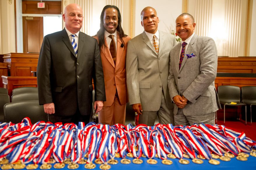 Left to right: Thomas P. McDevitt, President of the Washington Times Newspaper, Verdine White, of the band Earth, Wind, and Fire, Paxton Baker, Congressional Award Board Chairman, and Ralph Johnson, of the band Earth, Wind, and Fire, pose in front of Congressional Award Gold Medals before an award ceremony in the Cannon House Office Building on Capitol Hill, Washington, D.C., Wednesday, June 20, 2012. The 276 youth honored this year in the annual award ceremony for completing 400 hours of Voluntary Public Service activities, 200 hours each of Personal Development and Physical Fitness activities, as well as an Expedition and Exploration activity were greeted by members of congress as well as Verdine White and Ralph Johnson, two members of Earth, Wind, and Fire. (Andrew Harnik/The Washington Times)