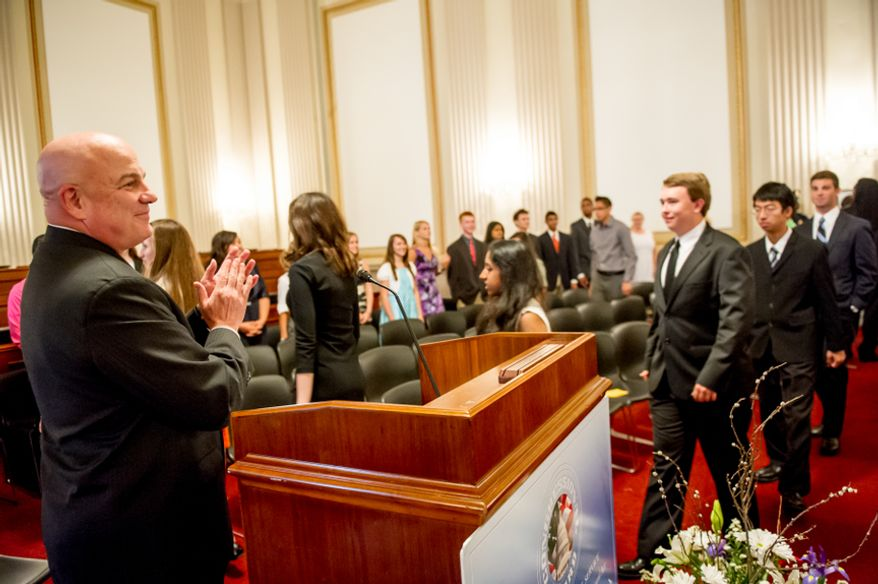 Thomas P. McDevitt, President of the Washington Times Newspaper, left, welcomes youth before they are awarded the Congressional Award Gold Medal during an award ceremony in the Cannon House Office Building on Capitol Hill, Washington, D.C., Wednesday, June 20, 2012. The 276 youth honored this year in the annual award ceremony for completing 400 hours of Voluntary Public Service activities, 200 hours each of Personal Development and Physical Fitness activities, as well as an Expedition and Exploration activity were greeted by members of congress as well as Verdine White and Ralph Johnson, two members of Earth, Wind, and Fire. (Andrew Harnik/The Washington Times)