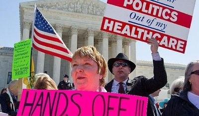 **FILE** Kathy Hansen, a family practice doctor in Houston, protests President Obama's health care law outside the Supreme Court on March 27, 2012. The justices were listening to arguments on the law's individual mandate. (Barbara L. Salisbury/The Washington Times)