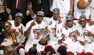 Miami Heat shooting guard Dwyane Wade holds the the Larry O'Brien NBA Championship Trophy, and small forward LeBron James holds his MVP trophy during a team picture with power forward Chris Bosh, point guard Norris Cole, and guard Terrel Harris, from left, after Game 5 of the NBA finals against the Oklahoma City Thunder, Friday, June 22, 2012, in Miami. The Heat won 121-106 to become the 2012 NBA Champions. (AP Photo/Lynne Sladky)