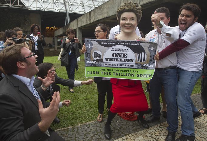 """Environmental activists, one portraying Brazilian President Dilma Rousseff holding a banner symbolizing """"dirty money"""" made from fossil fuel subsidies, protest on the final day of the United Nations Conference on Sustainable Development, or Rio+20, in Rio de Janeiro, Brazil, Friday, June 22, 2012. (AP Photo/Andre Penner)"""