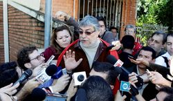 """Fernando Lugo, Paraguay's former president, talks to reporters outside his home in Lambare, on the outskirts of Asuncion, on Sunday, two days after Mr. Lugo was impeached and removed from office. He denounced the action as a """"parliamentary coup."""" He exhorted his followers to remain peaceful as they hold protests. (Associated Press)"""