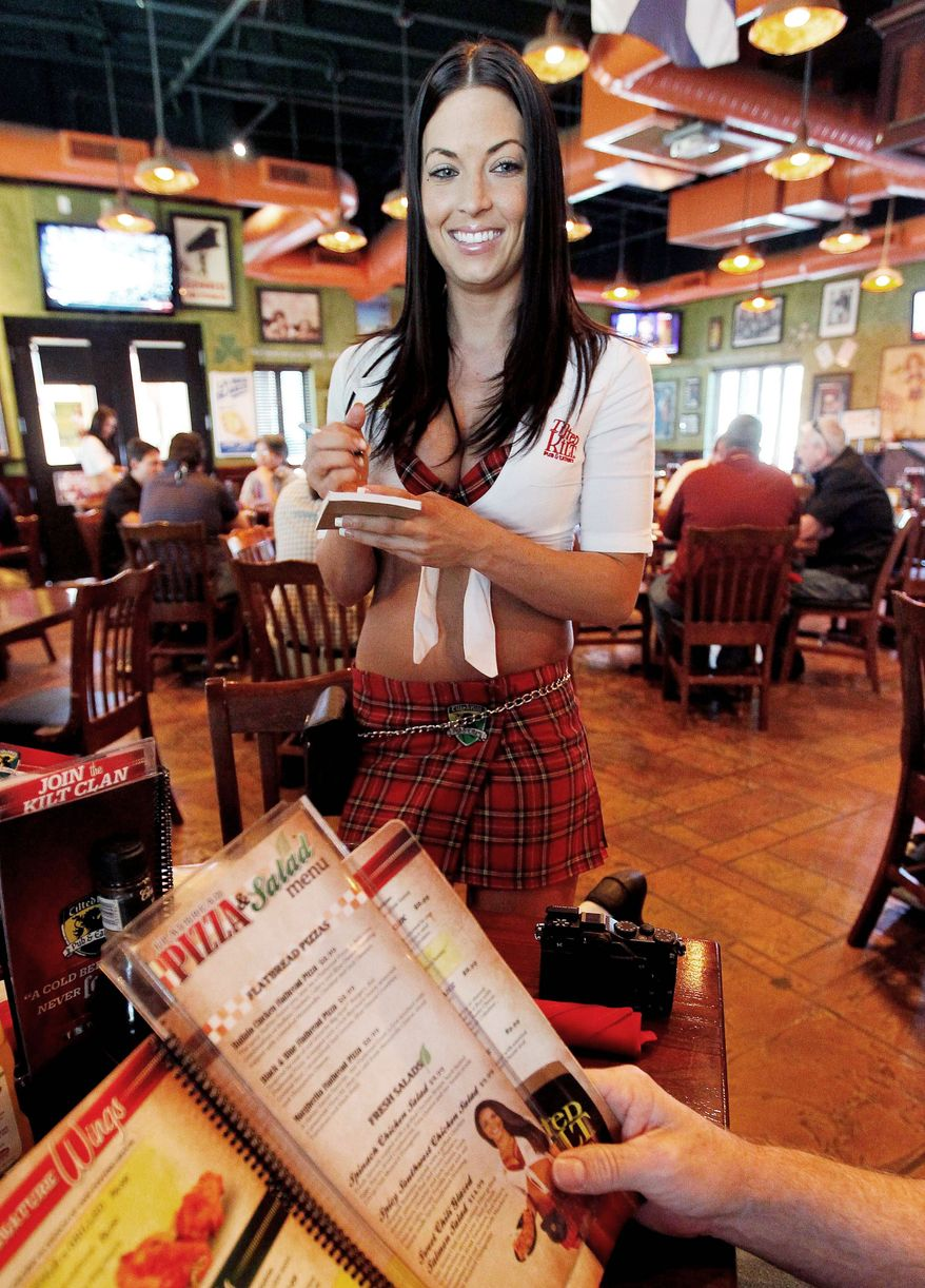 """Ashley Carpenter takes lunch orders at the Tilted Kilt, in Tempe, Ariz. The eatery is part of a booming niche in the restaurant industry known as """"breastaurants"""" or sports bars that feature scantily clad waitresses. These small chains are copying the business model of Hooters, which pioneered the concept starting in the 1980s. (Associated Press)"""
