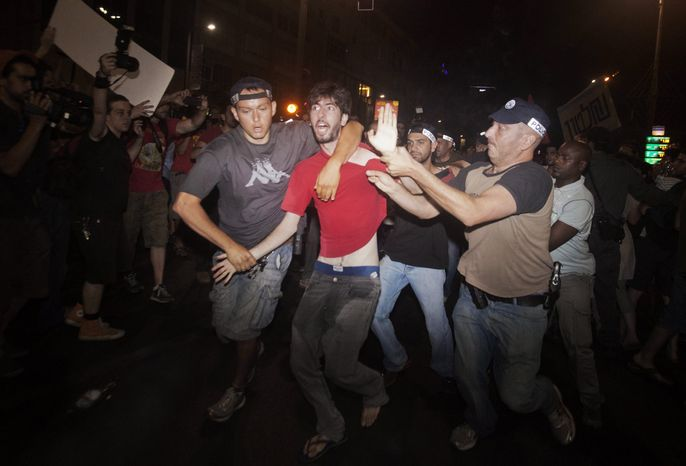 Israeli police detain an activist during a social protest in Tel Aviv early on Sunday, June 24, 2012. (AP Photo/Dan Balilty)