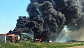 Smoke rises from two freight trains that collided two miles east of Goodwell, Okla., on Sunday, June 24, 2012. (AP Photo/The Guymon Daily Herald, Trudy Hart)