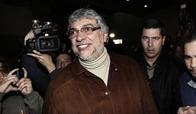 Former Paraguayan President Fernando Lugo (center) smiles after talking with his followers outside the Public Television building in downtown Asuncion, Paraguay, in the early hours of Sunday, June 24, 2012. (AP Photo)