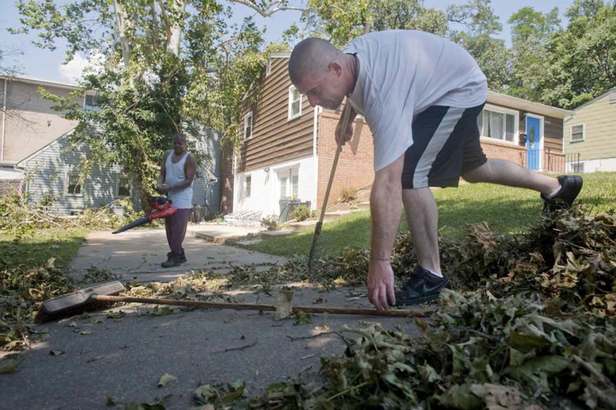 Residents Josh Ferguson, right, and John John Wolfe, left, help clean their front yard on Sunday, June 24, 2012, in Bladensburg, Md.  (Raymond Thompson/The WashingtonTimes)
