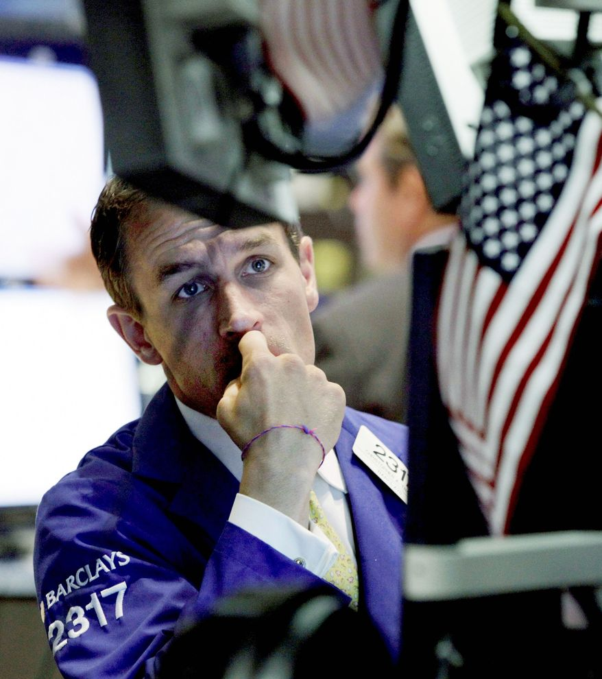 Specialist Christopher Trotta works on the floor of the New York Stock Exchange Monday. Stocks fell in both Europe and the U.S. (Associated Press)