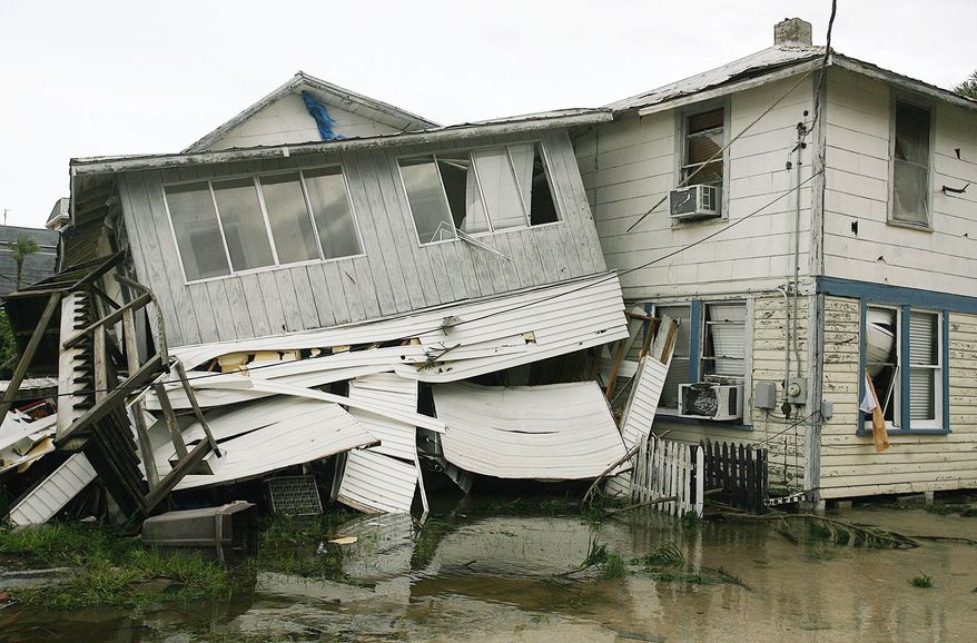 Jim Hall, 56, (left) and Dan Stephenson, 50, help an Imperial Estates neighbor salvage valuables from a home south of Brooksville, Fla., on Monday, after Tropical Storm Debby dumped heavy rain on the area. At least one person was killed Sunday by a tornado spun off by Debby in Florida. (Tampa Bay Times via Associated Press)