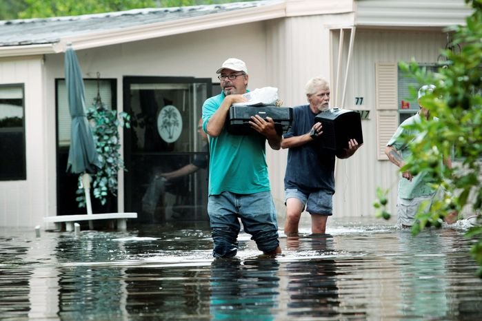A home lifted from its foundation sits next to a flooded yard in St. Pete Beach, Fla., on Monday. Gov. Rick Scott has declared a statewide emergency as an estimated 35,000 homes and businesses have lost electricity due to the slow-moving storm. (Tampa Bay Times photographs via Associated Press)