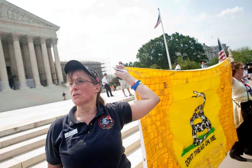 ** FILE ** Judy Pepenella, a New York resident and member of the Conservative Society for Action, protests the health care reform law Monday outside the U.S. Supreme Court. She said she is part of a group of 50 doctors who filed a friend-of-the-court brief advocating that so-called Obamacare be struck down. (Raymond Thompson Jr./The Washington Times)