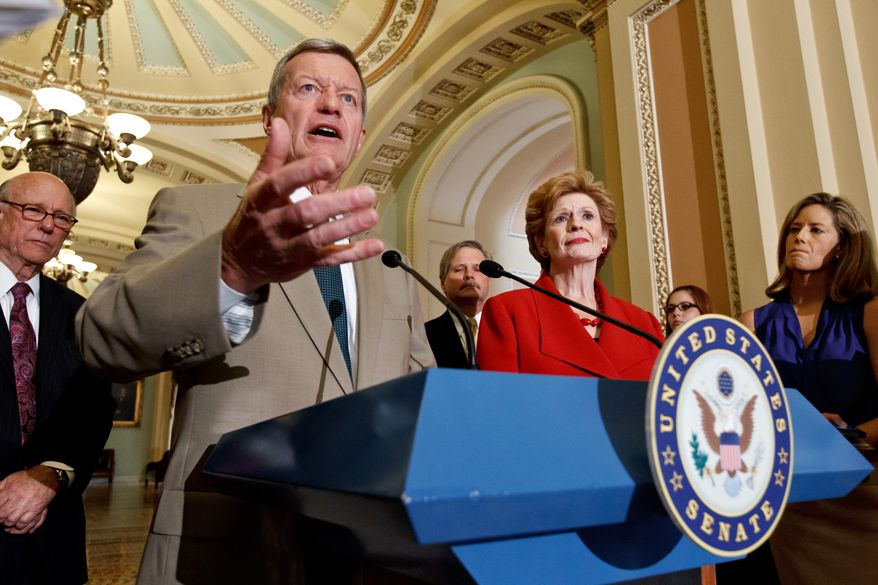 **FILE** Members of the Senate Agriculture, Nutrition and Forestry Committee praise the bipartisan passage of the Farm Bill at the Capitol in Washington on June 21, 2012. From left are Sens. Pat Roberts, Kansas Republican, Max Baucus, Montana Democrat, John Hoeven (rear), North Dakota Republican, and committee chair Debbie Stabenow, Michigan Democrat. (Associated Press)