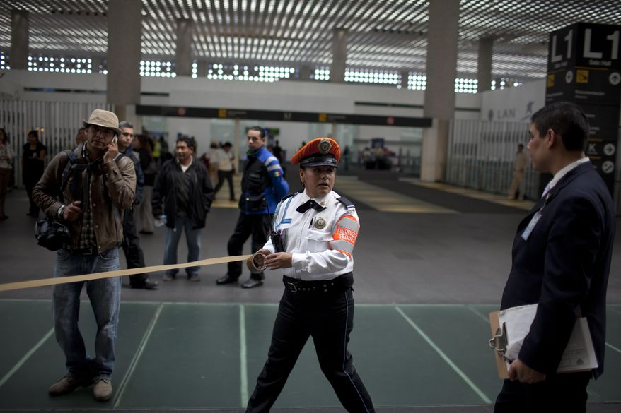An police officer cordons off the scene of a shooting at Mexico City's international airport on Monday, June 25, 2012. (AP Photo/Alexandre Meneghini)