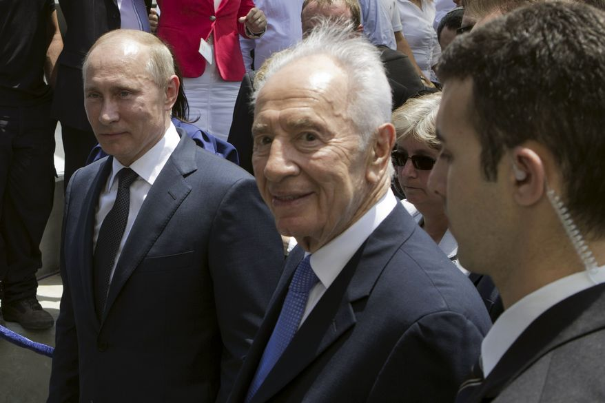 Russian President Vladimir Putin (left) and Israeli President Shimon Peres (center) leave after the inauguration ceremony of a memorial to Red Army veterans of World War II in Netanya, Israel, on Monday June 25, 2012. (AP Photo/Jack Guez, Pool)