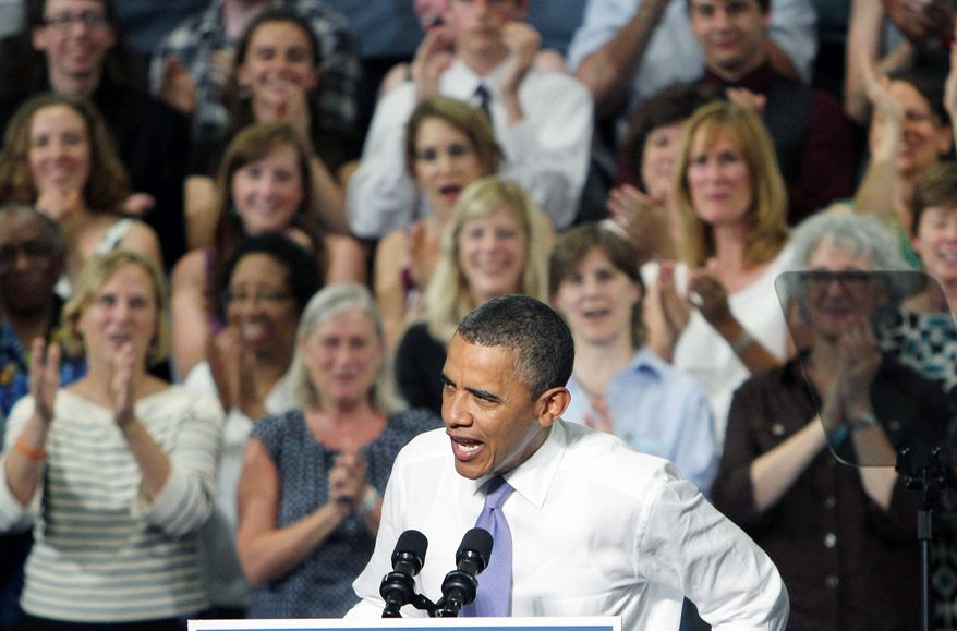 President Obama speaks at the Oyster River High School gym in Durham, N.H., on Monday. Mr. Obama appeared ebullient despite the overwhelming heat inside the gym. (Associated Press)