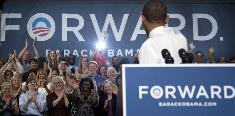 President Obama turns to wave to the people on the stage as he speaks June 25, 2012, at Oyster River High School in Durham, N.H. (Associated Press)
