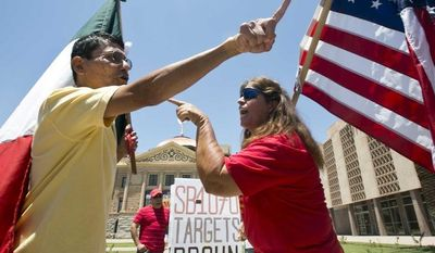 Andy Hernandez (left), carrying a Mexican flag, and Allison Culver, carrying an American flag, argue June 25, 2012, over SB1070 outside the State Capitol Building in Phoenix. (Associated Press/Arizona Republic)
