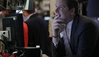 Specialist Gregg Maloney works June 25, 2012, on the floor of the New York Stock Exchange. (Associated Press)
