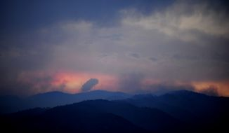 Wildfires burn west of Colorado Springs, Colo. on Sunday, June 24, 2012, as the sun sets. (AP Photo/Colorado Springs Gazette, Susannah Kay)