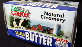 """The new logo is displayed on a package of butter made by the Cabot Creamery Cooperative. A green outline of Vermont has been dropped in favor of a green barn and the words """"Owned by our Farm Families in New York & New England."""" (Associated Press)"""