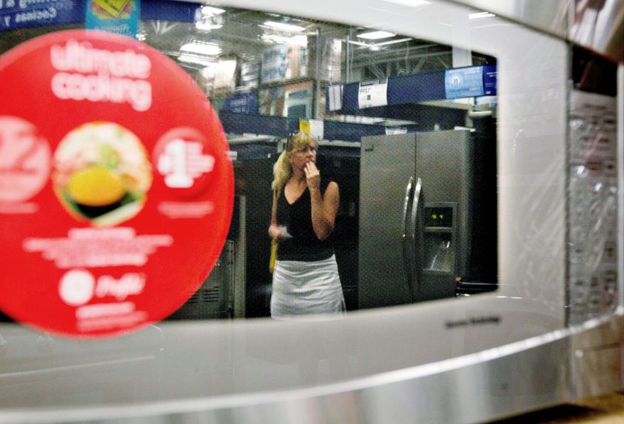 A shopper is reflected in a microwave oven on display at a Lowe's store in Atlanta. Consumer confidence fell in June for the fourth month in a row, according to the Conference Board, despite lower gas prices. Housing prices rose. (Associated Press)