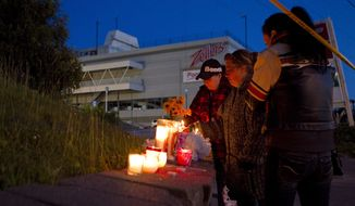 Well-wishers leave candles at a vigil on June 25, 2012, at the site of the collapsed roof of the Algo Centre Mall in Elliot Lake, Ontario, as rescue workers continue attempts to secure the building before searching for any survivors. (Associated Press/The Canadian Press)