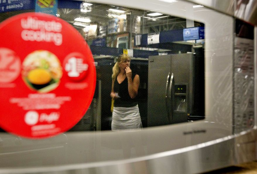 A shopper is reflected on a microwave oven on display on a showroom floor at Lowe's in Atlanta on Tuesday, June 19, 2012. (AP Photo/David Goldman)